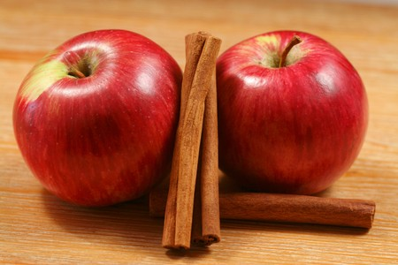 Apples and cinnamon sticks - two juicy fruits on the wooden table photo
