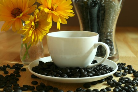 porcelain flower: Cup of black coffee and beans. Composition with flowers