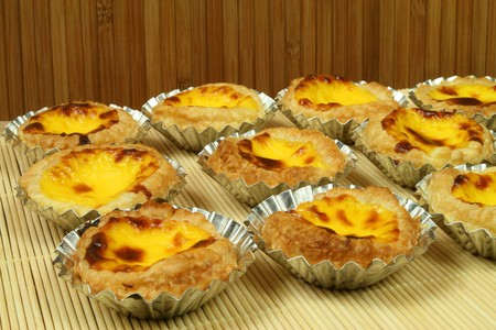 portugese: Traditional portugese egg tarts - pastries pasteis de nata in tin moulds Stock Photo