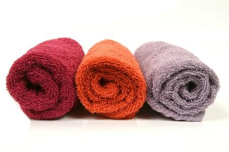 orange washcloth: Three colorful towel rolls on white background