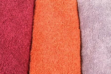orange washcloth: Background of three colorful towel rolls - orange, maroon and violet Stock Photo