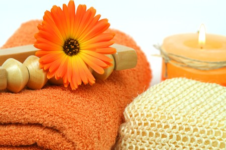 Spa tools in orange color - towel, marigold flower and burning candle