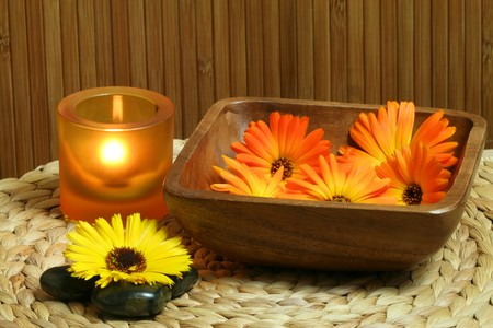 Beautiful natural spa composition. Marigold flowers in wooden bowl, zen stones and candle light photo