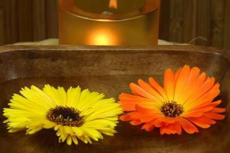 Two marigolds - yellow and orange, floating on woter in wooden bowl. Therapeutic calming spa treatment photo