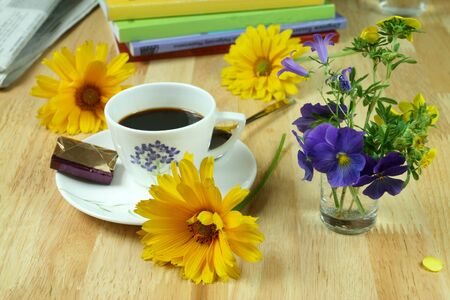 A cup of morning coffee surrounded with newspaper, colorful flowers and books. Optimistic day. photo