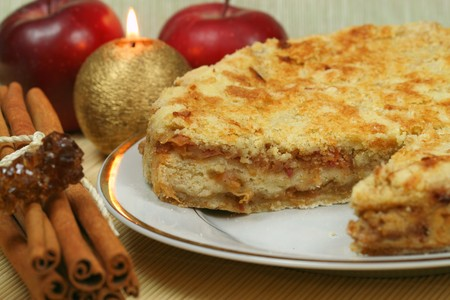 Home made apple pie with apples and cinnamon. Evening Christmas atmosphere - subdued light and candle