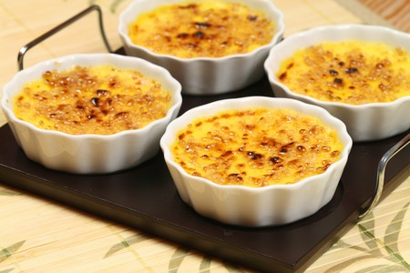 Four ramekins with french golden dessert - creme brulee on tray