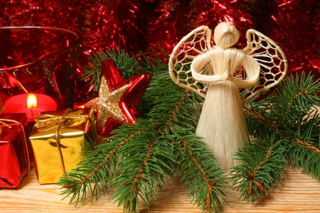Praying angel in Christmas tree branches with Christmas red ornaments photo