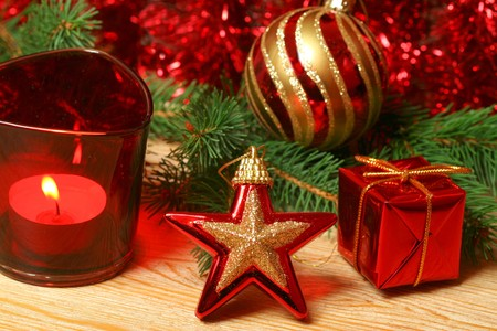 Christmas ornaments in red color - star, gift box, candle and glass ball with green alive Christmas tree branch photo