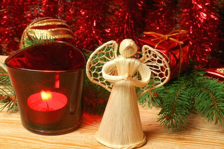 Angel in front of red Christmas wreath and candle photo