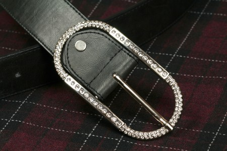 Closeup of silver belt buckle studded with dimond crystals on chequered wool fabric. Luxury and casual fashion photo