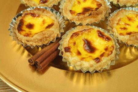 nata: Traditional portuguese egg tarts - pastries pasteis de nata on golden plate with cinnamon sticks