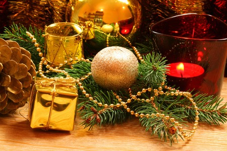 Christmas wreath with golden ornaments - glass ball, Christmas present and candle in red holder photo