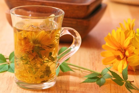 precipitate: Freshly brewed healthy herbs in glass - marigold flowers, thyme and St. Johns Wort. Healing tea for chill