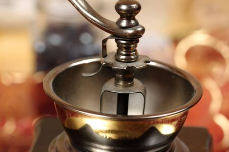 hand crank: Closeup of part of old-fashioned hand coffee grinder - brass bowl and crank