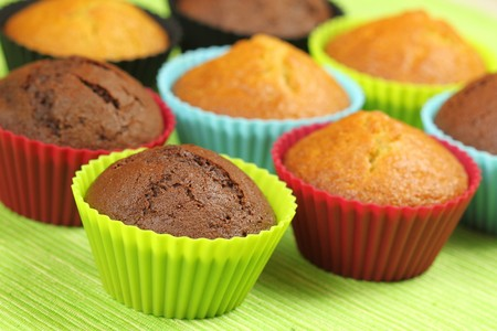 Muffins in colorful silicon moulds on green background photo