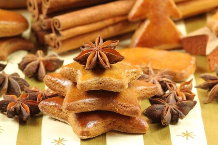 Gingerbread cookies - Christmas tree shape made of stars. Whole aniseed and cinnamon sticks photo