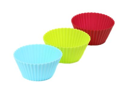 Set of three colorful silicon moulds for muffins over white  photo