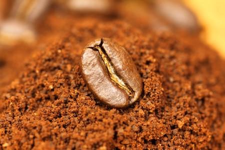 Closeup of arabic coffee bean on ground coffee photo