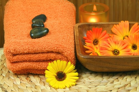 Spa therapy with orange marigold flowers. Massage tools photo