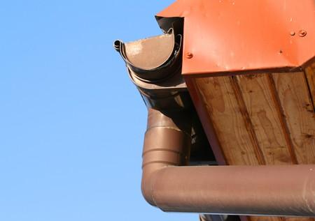 gouttière: Goutti�re de la pluie sur la maison avec un ciel bleu dans le bakcground Banque d'images