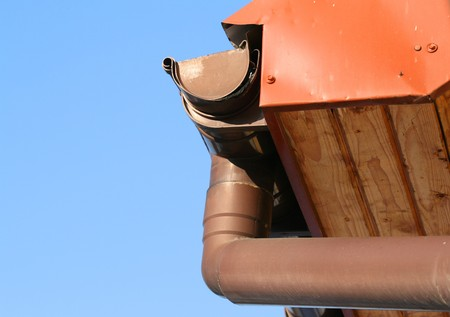 overhang: Rain gutter on house with blue sky in the bakcground