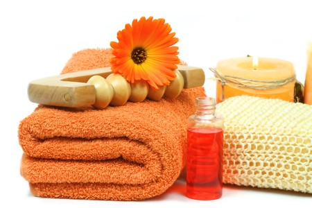 Spa accessories in orange colour with beautiful marigold flower over white