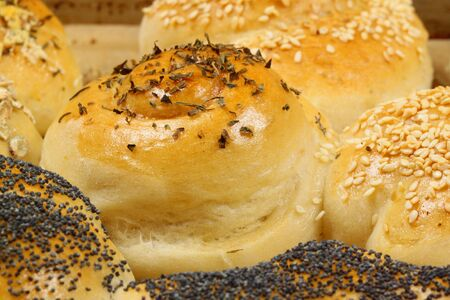 tinplate: Fresh baked salty buns various shaped with herbs, poppyseed and sesame on tinplate Stock Photo