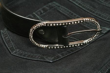 zircon: ladys silver belt buckle studded with zircon crystals on jeans background. Luxury and casual