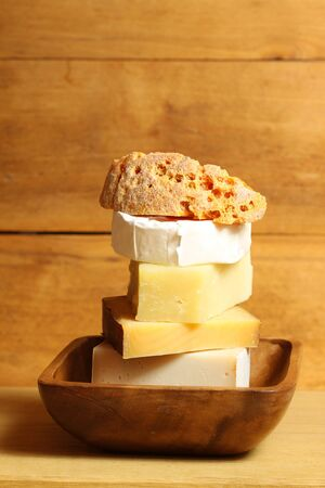 Different types of cheese in rustic scenery. Pile of cheese in wooden bowl photo