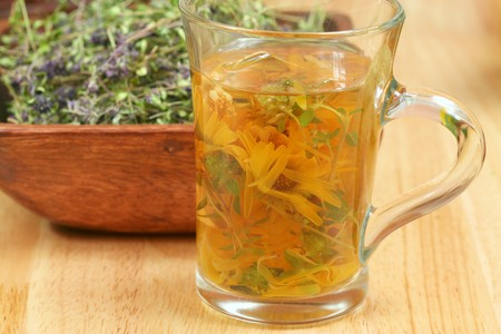 Glass of infused herbs and dried thymus in background. For cough Stock Photo - 7693696