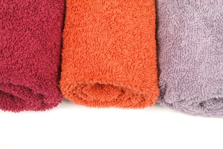 orange washcloth: Three colorful towels in rolls over white Stock Photo
