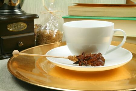 White coffee cup with sugar stick, grinder and books photo