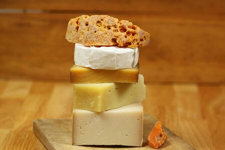 Stack of different kinds of cheese on wooden board - goat cheese, mimolette and camembert photo