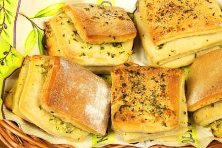 Closeup of home made layered bread rolls filled with garlic, butter and parsley in basket photo