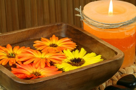 Orange marigold flowers floating in wooden bowl, burning candle and stones. Spa still life photo