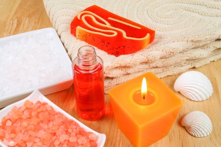 Energetic orange spa therapy composition  - candle, salt crystals and seashells photo
