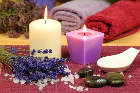 Composition of dried lavender, seasalt and massage stones with burning candles. Spa still life photo