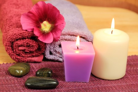 Spa composition in heath color with burning candles, stones and holyhock flower photo