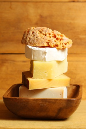 Cheese tower - various kinds in wooden bowl. Vertical photo