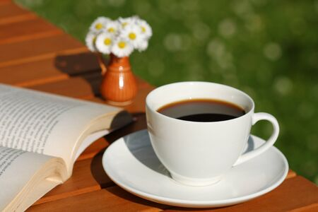 Black coffee in white cup, book and bunch of daisies. Leisure time in the garden photo