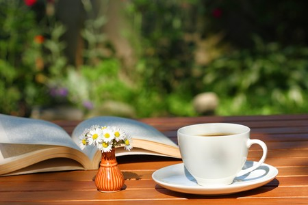 marguerite: Café et un livre sur la table de jardinage