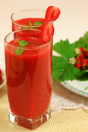 Two glasses with red strawberry smoothie with fresh fruits photo