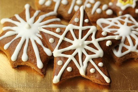 Gingerbread stars with white icing decoration on golden plate. Beautiful Christmas cookies