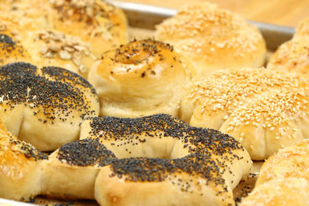 tinplate: hot home-made bread rolls sprinkled with seeds on tinplate Stock Photo