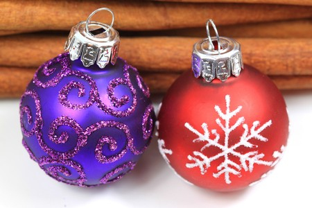 cinnamon sticks: Two ornamented decorative Christmas glass balls and cinnamon sticks behind Stock Photo
