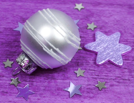Bright glass bauble ornament and stars. Purple colors background Stock Photo - 8379370