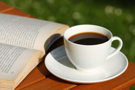 Drinking black strong coffee in the garden and reading book photo