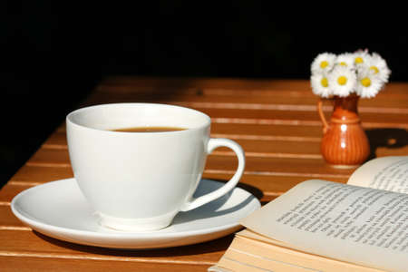 Coffee and book with beautiful daisies bouquet in small vase photo