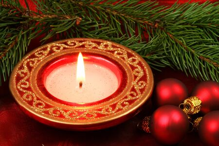 Christmas candle and baubles in conifer wreath photo